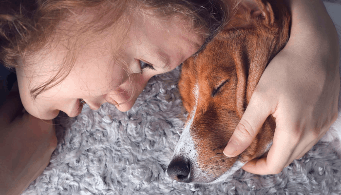 A girl sleeping with a dog with her hand on the dog's chin.